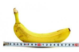 Large banana and measuring tape on white background